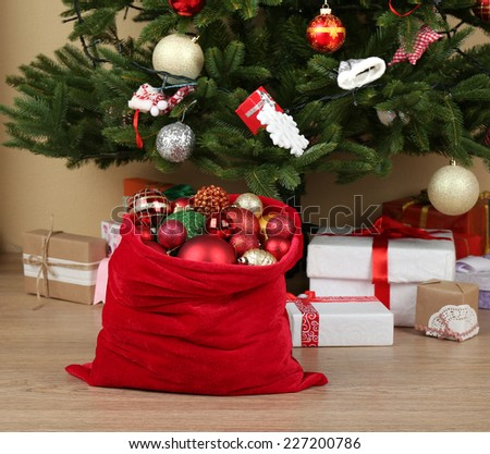 Red bag with Christmas toys and gifts in room