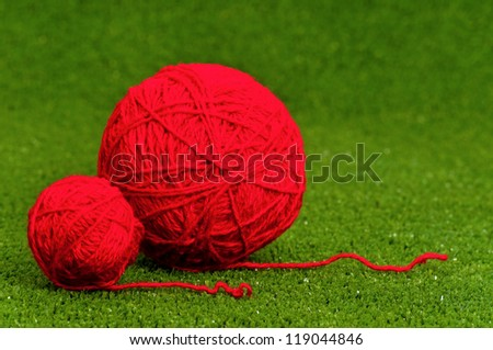 Red ball of yarn on green artificial grass - stock photo
