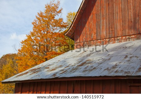 Red barn in autumn forest at dawn