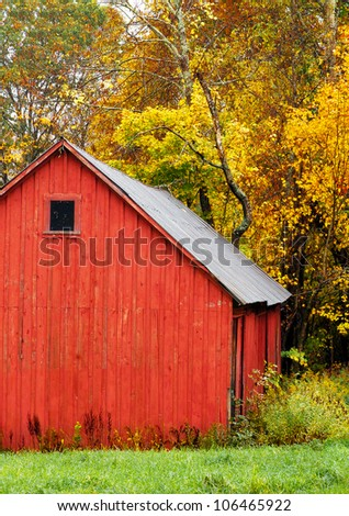 Red barn in autumn, with a background of colorful trees and fall leaves. Vertical. - stock photo