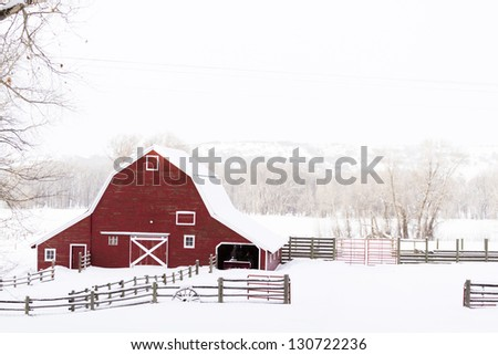 Red barn in snow on lamb farm. - stock photo