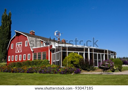 Red barn with an attached sunroom to enjoy those nice summer days - stock photo