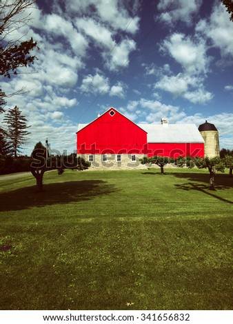 Red barn with apple trees in front. - stock photo