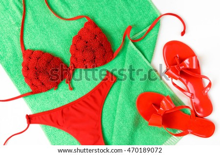 Red bathing suit and red flip-flops on green towel. Summer clothes.