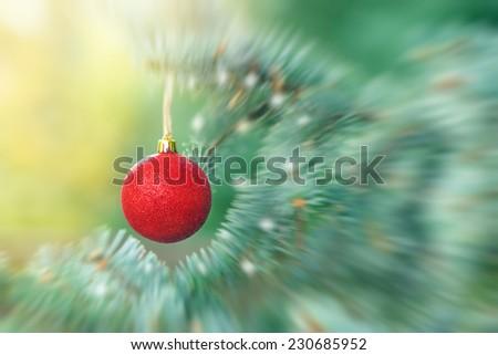 Red bauble on Christmas tree (xmas ball, christmas ornament) - stock photo