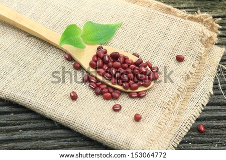 Red Bean on bamboo wooden spoon, green leaf and gunny-bag at Bangkok, Thailand. - stock photo