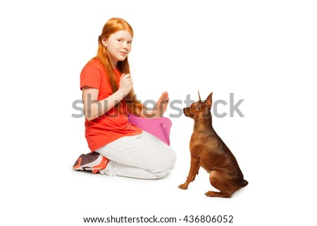 Red beautiful girl taming and training dog