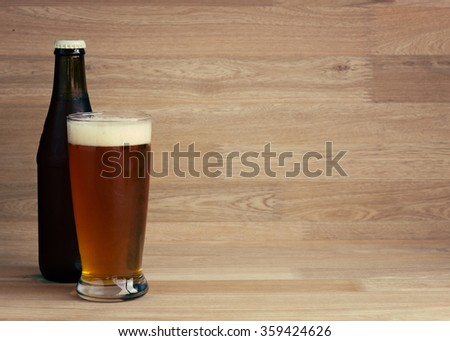Red beer in glass and bottle over wood