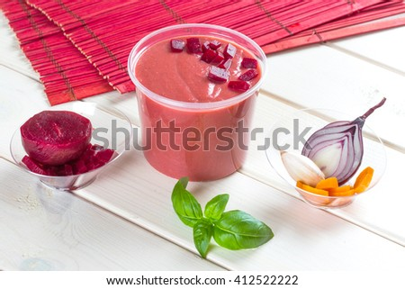 Red beetroot cream soup with pieces of beet and onion - stock photo