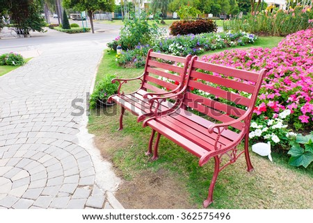 Red bench in a flower garden. - stock photo