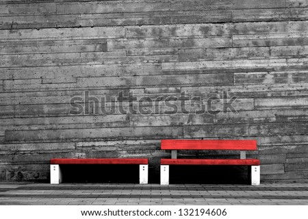 Red benches contrasted against dull concrete wall. - stock photo