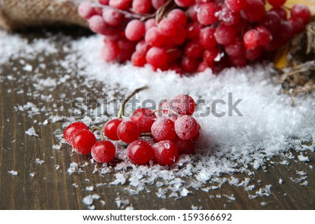 Red berries of viburnum and snow on sackcloth napkin, on wooden background - stock photo