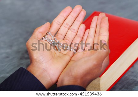 Red bible lying on blue desk with mans open hands above book, rosary cross placed inside, religion concept - stock photo