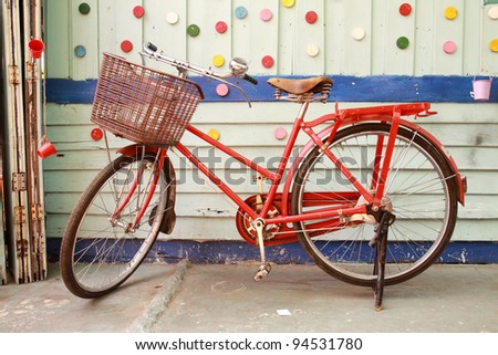Red bicycle and colorful wood wall