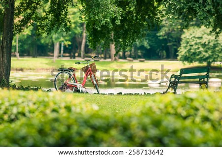 Red bicycle in fresh summer park - stock photo