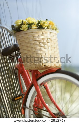 Red bicycle leaning against fence. - stock photo