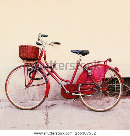 Red bicycle with wicker basket in old Italian town. Color toning effect was applied. - stock photo