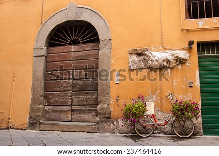 Red bike loaded with flowers standing in front of an old wooden door in a traditional Italian medieval city center. Tuscany, Italy. - stock photo