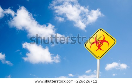 red Biohazard or Bio Hazard symbol Road Sign on blue sky - stock photo