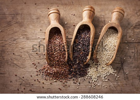Red, black and white quinoa seeds on a wooden background - stock photo
