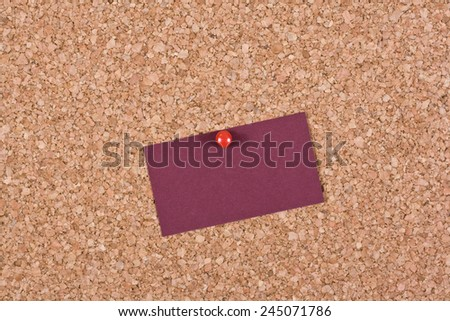 Red blank business card attached to a cork board - stock photo