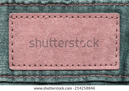 red blank leather  label on green jeans background - stock photo