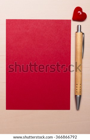 Red blank sheet of paper with heart love symbol and pen on wooden surface. Background for valentines day or wedding card. - stock photo