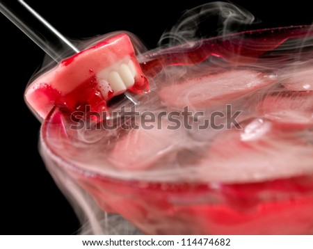 Red bloody cold cocktail with vampire teeth