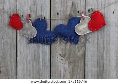 Red, blue and wood hearts hanging on clothesline with wood background - stock photo