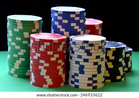 Red, blue, green, white and black poker chips columns
