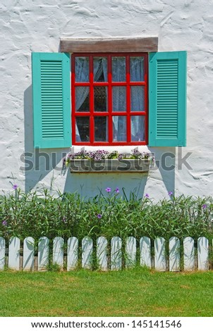 Red & Blue Window with flower pots on the white wall background.