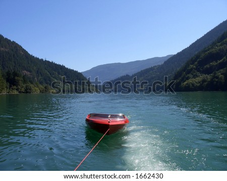 Red boat being towed - stock photo