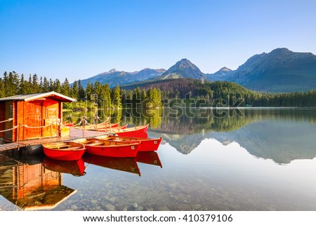 Red boats moored at wooden house on a lake with a clear  water against the background of high mountains. Strbske Pleso lake, Slovakia, Tatra mountains.  - stock photo