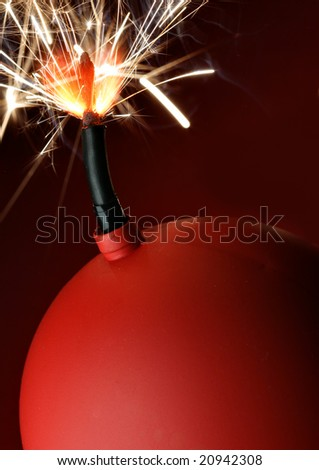 Red bomb with burning fuse close-up - stock photo