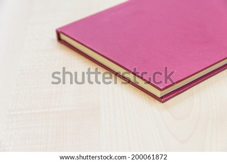 Red book on a wooden table.
