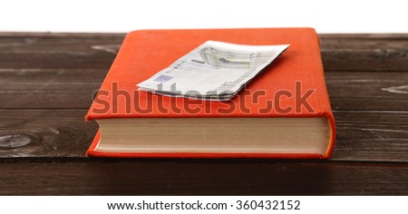 Red book with euro banknotes on white background. Stash of money - stock photo