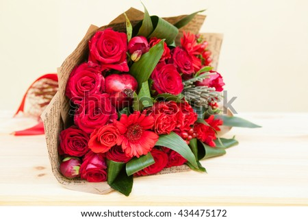 Red bouquet of roses, gerberas, peonies, pomegranates. Love and passion symbol. Anniversary or birthday gift for girl. - stock photo