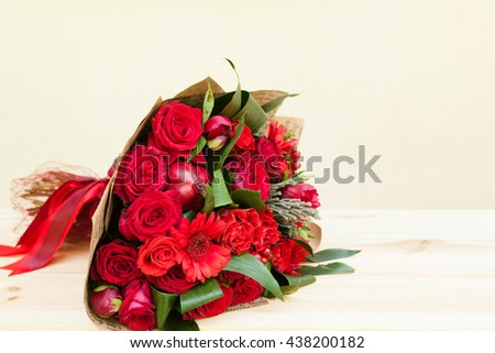 Red bouquet of roses, gerberas, peonies, pomegranates with copy space. Love and passion symbol. Anniversary or birthday gift for girl. - stock photo