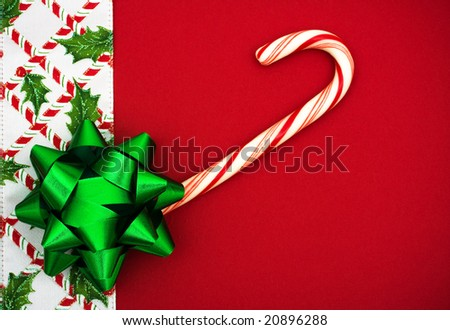 Red bow and candy cane with holly berries and leaf border on red background, Christmas border - stock photo