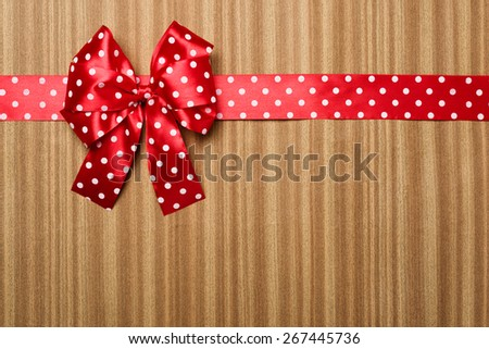 red bow on wooden background - stock photo