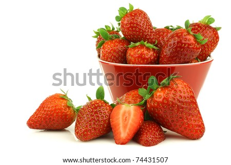 red bowl full of fresh strawberries and a cut one on a white background - stock photo