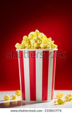Red bowl full of popcorn on red background for film, TV, television watching. Concept of movie night - stock photo