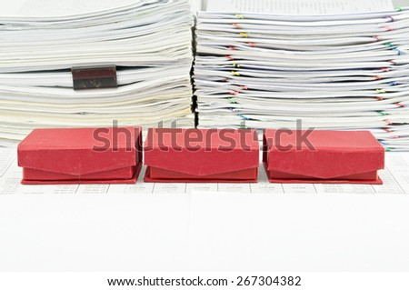 Red box arrange on finance account with pile of paperwork as background. - stock photo