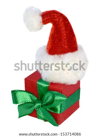 Red box with green bow and Santa furry cap on top - stock photo