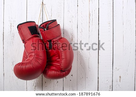 red boxing gloves hanging on the wall - stock photo