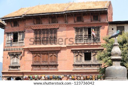 Red brick and thatch roof building with carved wooden windows and tibetan flags, hindu and buddhist  masks on the grooundfloor, Swayambhunath Stupa area, Kathmandu, Nepal. - stock photo