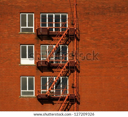 Red brick building with three rows of windowed fire escapes - stock photo