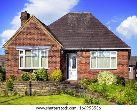 Red brick house with garden - stock photo