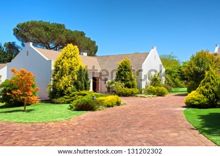 Red brick square in front of white house. Shot near Kuilsriver/Cape town, Western Cape, South Africa. - stock photo