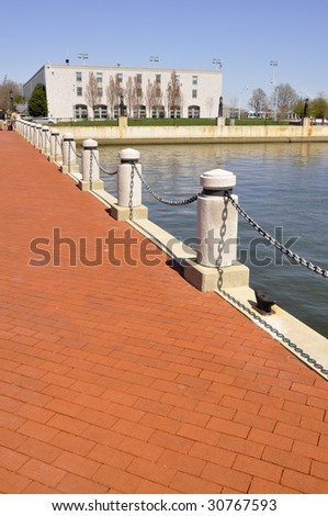 red brick walkway by the water and the United States Naval Academy in Annapolis, Maryland - stock photo
